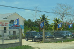 The flag of Belize flying at A.Q. Belize Auto Rentals 4 Less in Central America (RYANISLAND) Tags: city america belize central tropical tropic belizecity tropics centralamerica warmweather centralamerican belizean belizeanpeople countyofbelize
