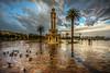 The rain (Nejdet Duzen) Tags: trip travel sunset reflection rain turkey square cloudy pigeon türkiye palm clocktower palmiye konak izmir günbatımı güvercin yansıma meydan turkei seyahat yağmur saatkulesi bulutlu