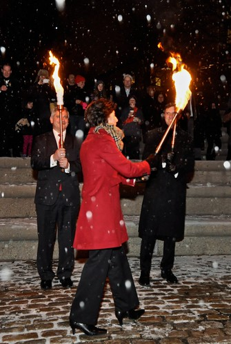 Governor Gina Raimondo lighting the torches of Lt. Governor Dan Mckee and Treasurer Seth Magaziner in the Snow. Photo by Luis Andrade.