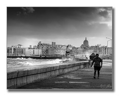 A stormy Malecn (Descended from Ding the Devil) Tags: sea sky blackandwhite bw storm monochrome clouds buildings waves havana cuba kitlens spray walker malecon puddles hombre lahabana elcapitolio photoborder canon40d