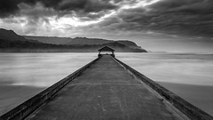Hanalei Pier in Black&White (PIERRE LECLERC PHOTO) Tags: longexposure travel sea blackandwhite mountains beach water walking landscape hawaii pier moody structure pacificocean kauai boardwalk hanaleipier drama hanalei picnictable hanaleibay pierreleclercphotography