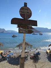 pirate's beach (squeezemonkey) Tags: kalymnos greece piratesbeach beach sign sea boats islands sand bathers sunbeds