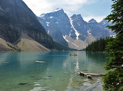 Moraine Lake tranquility (karma (Karen)) Tags: trees canada mountains topf25 reflections boats lakes driftwood pines canoes alberta 4summer morainelake canadianrockies banffnp 50favs canadanationalparks