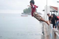 Jumping off a bridge... (Syahrel Azha Hashim) Tags: travel light boy vacation holiday detail island 50mm prime jump nikon colorful dof audience getaway naturallight malaysia handheld shallow pahang tiomanisland jumpingoffabridge boyjumping d300s syahrel
