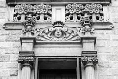 The Girl Over the Door (Colorado Sands) Tags: barcelona door blackandwhite espaa building monochrome face architecture spain europe exterior decoration catalonia doorway catalunya espagne faade sandraleidholdt exteriortrim