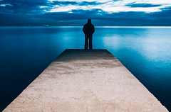 Man is standing on a jetty looking the sunset (k_maxim) Tags: contemplation dreams men solitude loneliness pier jetty oneperson meditating sunset silhouette sea people landscape nature standing lookingatview scenics individuality freedom hope sky vacations spirituality sensuality lifestyles tranquilscene beautiful traveldestinations yellow thenaturalworld afterwork silence harmony sunlight idyllic romanticsky leisureactivity break lifestyle landscapes summer