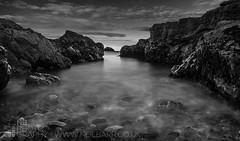 Rocks at Dunbar (GenerationX) Tags: longexposure sea sky bw white black beach water mono rocks waves unitedkingdom horizon pebbles dunbar eastlothian