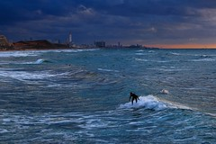 surfing in the rough sea at sunset (Lior. L) Tags: travel winter light sunset sea sky storm motion water weather sport skyline clouds canon buildings israel telaviv movement mediterranean waves action surfer horizon stormy surfing telephoto rough canondslr mediterraneansea telephotolens stormyweather actionshot watersport canon70200f4l seastorm extream actionphotography roughsea cloudysunset extreamsport winterinisrael horizonbeach canon600d travelinisrael canont3i canonkiss5 surfingintheroughseaatsunset
