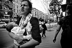 A Look of Despair on a Nursing Mother (stimpsonjake) Tags: city blackandwhite bw baby monochrome walking mom infant candid streetphotography highcontrast romania worried breastfeeding bucharest nursing 185mm nursingmother nikoncoolpixa