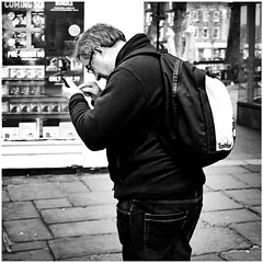 Extreme close-up (mesonparticle) Tags: england blackandwhite bw man glasses phone shortsighted streetphotography cellphone backpack mobilephone salisbury spectacles texting x100t