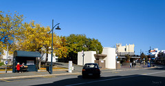 Waiting for Her Bus (Jocey K) Tags: street autumn trees newzealand sky people cars lamp architecture buildings shadows busstop timaru southcanterbury tripdownsouth