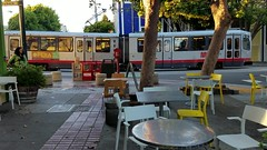 Duboce. (A National Acrobat) Tags: blue trees red sunlight green cars bike yellow chairs muni tables bicyclist njudah dubocepark duboce steiner duboceparkcafe