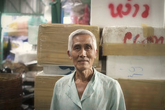 Krung Thep, the city of angels (slow paths images) Tags: travel portrait man face pose asian thailand asia southeastasia bangkok oldman indoors thai worker boxes gaze flowermarket artificiallight workenvironment krungthep thecityofangels fredcan