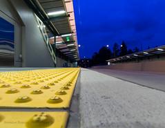 Pinwheel (Brendinni) Tags: street new blue urban yellow metal clouds design shiny dof bokeh pov low cement corridor safety transit grooves blueskies bluehour sparkling urbanlandscape sr520 relective 520transitstation