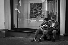 Father and Son (Leanne Boulton) Tags: monochrome people urban street candid portrait streetphotography candidstreetphotography streetlife man men male boy child father parent dad face faces facial expression parenthood mobile phone reflection sitting watching tone texture detail natural outdoor light shade shadow city scene human life living humanity society culture canon 7d 35mm black white blackwhite bw mono blackandwhite glasgow scotland uk