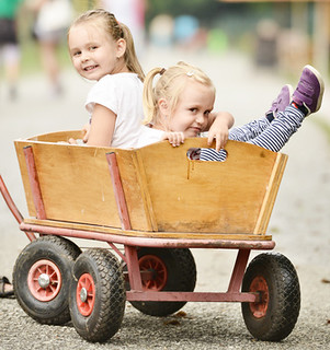 2 little girls riding in wooden wagon