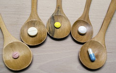 Pills with wooden spoon on wood background. (Health Units) Tags: pain closeup aspirin pharmacist natural pharmaceutical green medical drugs herbal pill concept overdose leaf laboratory druggist dosage medicinal medicament old treatment ill spoon painkiller medication medicine macro wood turmeric healthy hospital care vitamin cure illness capsule poison herb wooden health nature prescription pharmacy healthcare