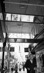 Reflected (4foot2) Tags: street leica people blackandwhite bw reflection film glass monochrome look shop lady 35mm shopping manchester mono women kodak guess candid trix streetphotography rangefinder lookingup reflected summicron 35mmfilm diafine kodaktrix streetphoto shopwindow analogue m3 peoplewatching reportage wigan streetshot reportagephotography 2016 filmphotography 35mmf2 greatermanchester interestingpeople leicam3 1200iso manchesterpeople zonefocus 1200asa 35mmf2summicron 4foot2 candidportrate 4foot2flickr 4foot2photostream fourfoottwo