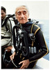 Cousteau seated in scuba gear. (Vintage Scuba) Tags: red man black men wet yellow fetish silver james us divers pants mask boots tail stripe gear scuba diving double hose beaver equipment suit jacket bond hood diver beavertail fin jacques booties striped fins wetsuit 007 regulator cousteau