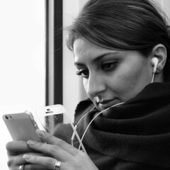 iPhone by Train (d_t_vos) Tags: portrait blackandwhite bw woman white playing black travelling apple face contrast train dark asian eyes hands mediterranean candid watching bn traveller nails listening earphone shawl youngwoman iphone facesofportraits dickvos dtvos