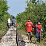 Two Boys Walking Alongside Bamboo Train Rail Tracks 1 thumbnail