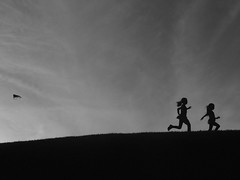 Running Sisters (Uniqueful) Tags: girls sky people blackandwhite bw white kite playing black monochrome silhouette kids sisters children fun outside outdoors flickr play outdoor hill running run playful