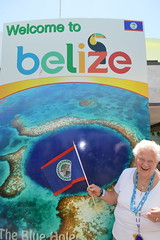 Theresa Irene Wolowski, waving the Belizean flag at the Welcome to Belize Central America sign (RYANISLAND) Tags: city america belize central tropical tropic belizecity tropics centralamerica warmweather centralamerican belizean belizeanpeople countyofbelize