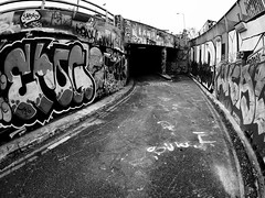 Leake Street (Cris Ward) Tags: street city urban blackandwhite distortion streetart london art monochrome thames architecture buildings underground subway graffiti town mural paint riverside wide streetphotography tunnel tags olympus monotone southbank fisheye waterloo spraypaint ultrawide walimex streetscenes omd csc greyscale throws 75mm samyang mirrorless leakestreet microfourthirds olympusomdem10 padtunnel