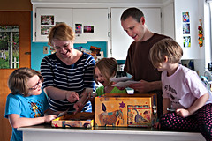 a family gathered in the kitchen at home looking at photographs (PersonalCreations.com) Tags: family house man home girl kids project children mom diy photo dad child photograph