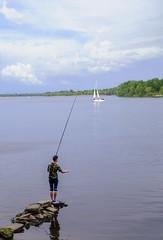 Fishing (Tanya Yakovchuk) Tags: boy lake fish water clouds rural relax outdoors fishing young relaxing lifestyle barefoot fisher shorts recreation