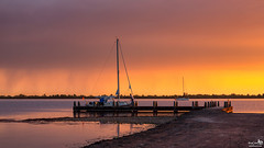 Golden light and colors at sunset (BraCom (Bram)) Tags: sunset cloud man holland netherlands rain sailboat canon boot evening pier boat spring zonsondergang widescreen jetty nederland silhouettes german nl avond showers 169 lente regen refelctions wolk zuidholland goereeoverflakkee voorjaar grevelingen steiger spiegeling southholland buien dirksland canonef24105mm veermansplaat slikkenvanflakkee zeilboat bracom canoneos5dmkiii bramvanbroekhoven