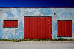 Garage ([dscphoto]) Tags: summer hot sunshine bluesky garage door industrial industrialpark ontario travel blue building architecture outdoor lines texture bright red abstract polarizer 18200 d7000 driveway grass windows goderich