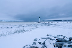 Stark (Thousand Word Images by Dustin Abbott) Tags: blue winter sky lighthouse snow ontario canada cold ice beautiful marina pembroke frozen rocks quebec handheld fullframe manualfocus marinescen