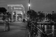 Close Encounters (McQuaide Photography) Tags: amsterdam noordholland northholland netherlands nederland holland dutch europe sony a7rii ilce7rm2 alpha mirrorless 1635mm sonyzeiss zeiss variotessar fullframe mcquaidephotography adobe photoshop lightroom tripod manfrotto light licht night nacht nightphotography longexposure stad city capitalcity urban lowlight architecture outdoor outside old oud amstel grachtenpand canalhouse house huis huizen traditional authentic water reflection centrum gebouw building waterfront waterside tourism touristattraction travel bridge magerebrug skinnybridge brug blackandwhite bw mono monochrome