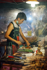 Young woman cooks fish and seafood (Evgeny Ermakov) Tags: asia asian chiangmai chinese thai thailand bbq chef cook cooking cuisine culture fish food foodstall fried grilled local market marketstall marketplace night nightmarket people seafood smoke stall street streetfood streetmarket traditional vendor walkingstreet woman young youngwoman editorialuse