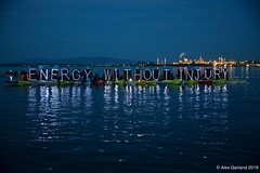 Large LED OLB Energy Without Injury light panel with Tesoro Refinery in background at Break Free PNW 2016 photo by Alex Garland img_1954 (Backbone Campaign) Tags: water justice washington energy kayak break action politics protest creative paddle shell free social demonstration oil change wa environment activism anacortes campaign pnw refinery climatechange climate tesoro artful backbone renewable refineries 2016 kayaktivist kayaktivism breakfreepnw