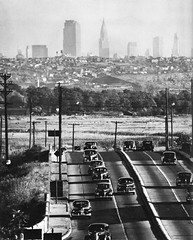 Drivers in 1930s and 1940s cars zip along through the Meadowlands swamps on Route 46 while the Chrysler Building and Midtown Manhattan hover in a different world. Not a hint of the NJ Turnpike in the distance. Bendix, New Jersey. 1942 (wavz13) Tags: urban blackandwhite skyline vintagecar noir skylines oldbuildings newyorkskyline manhattanskyline oldcar oldcars oldbuilding oldcity oldnewyork vintagecars newjerseyturnpike teterboro noire oldphotography oldcities oldhighway oldfords vintagebuilding vintagephotography collectablecars newyorkphotos swampsofjersey collectiblecars vintagenewyork newyorkphotographs newyorkphotography vintagebuildings oldchevys oldmanhattan 1940scars vintagechevies 1940sphotography vintagefords newjerseyhistory oldhighways newjerseyhighways vintagemanhattan 1930scars vintagecity newjerseyphotography olddodges vintagecities industrialnewjersey vintagenewjersey earlyhighways oldnewjersey vintagehighways newyorkskyscapers vintagechryslers oldnewyorkphotography oldnewyorkphotos newjerseyswamps