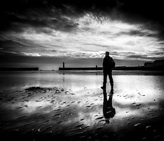 Its Yer Man Again   [Explored] (RonnieLMills) Tags: light blackandwhite bw lighthouse reflections mono sand harbour explore shade figure lone ripples vignette contrasty donaghadee 444 explored 11716