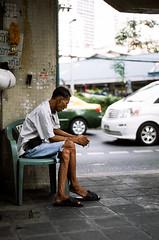 Tired man in Bangkok (etherlore) Tags: street travel man film analog 35mm thailand bangkok tired fujichrome nikonfe2 coolscanv nikkor50mmf18d fujichromeprovia100frdpiii ls50