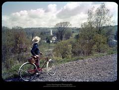 Guilford Center in May, 1959 (Sherwood Harrington) Tags: church bike bicycle steeple upstatenewyork cowboyhat vintageslide nyow chenangocounty newyorkontariowesternrailroad guilfordcenter lynnharringtonphotography