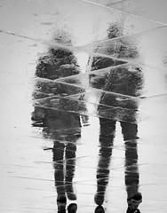 The couple (martina.stang) Tags: people reflection rain walking couple scheveningen paar sidewalk spiegelung womanandman schwarzweis inexplore