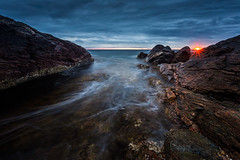 Blue Sea (Arvid Bjrkqvist) Tags: longexposure blue sunset sun water clouds rocks cloudy sweden horizon overcast rays bluehour clifs biskopshagen