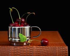 Elegant Presentation (njk1951) Tags: red summer cup blackbackground fruit book leaf cherries presentation oldbook espressocup redcherries stainlesssteelcup summercherries elegantpresentation shinycup