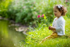 Sweet, happy little girl sitting on a grass in a park at a spring stream with flower in hand. Laughing, enjoying fresh air in forrest. (Tonya B4) Tags: child playing kid girl spring summer smiling garden park grass flowers outdoors small green fun cute season childhood meadow warm leisure happiness laughing adorable joy enjoyment cheerful nature little happy toddler stream water river beautiful curlyhair allergy aroma forrest breathing riverside waterside healthy chidlhood picnic caucasian background picturesque blossom family russianfederation