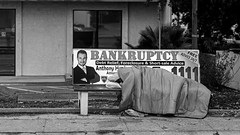 cruel irony (Robert Couse-Baker) Tags: poverty street city bw money bench suburban homeless busstop sacramento bankruptcy