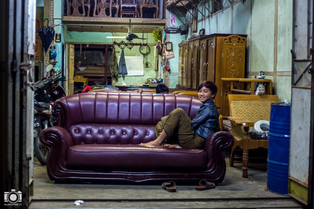 Un joven descansa en un almacén de muebles en Mandalay (Myanmar)