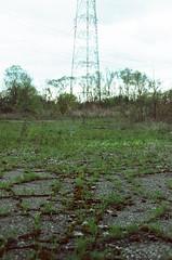 (pop archaeologist) Tags: city blur film grass vertical canon landscape weeds kodak bokeh michigan depthoffield flint eos5 electrictower 28105 gold200 abandonedlot eosa2 crackedasphalt