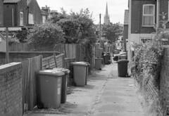 Accidie (Fray Bentos) Tags: alley norwich wheeliebins ilforddelta400 entry norwichcathedral terracedhouses fujifilmga645zi promicrol1910mins