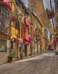 Toledo (Jan Kranendonk) Tags: spain town city buildings architecture historical sunny europe spanish sky clouds famous landmark traditional travel street banners flowers shops stores tourism hotel hostal pension accommodation festival corpus christi flags ngc