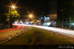 Red and White. Intersection in front of Bank BRI, Alun-alun Jember (Haris Riz'Q) Tags: road street city longexposure car bulb night canon indonesia landscape eos town downtown cityscape traffic photograph lighttrail jember 1100d momentwarrior kameradslrgw visitjember
